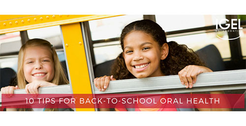 Two elementary school children smiling through a bus window.
