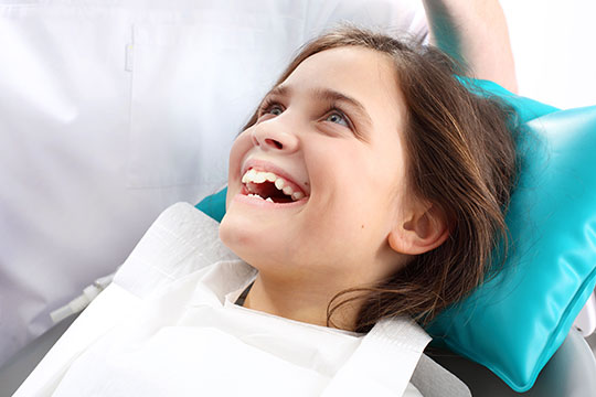 girl in a dental chair smiles at the dentist