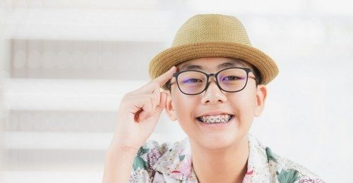 A young boy with glasses and braces smiling